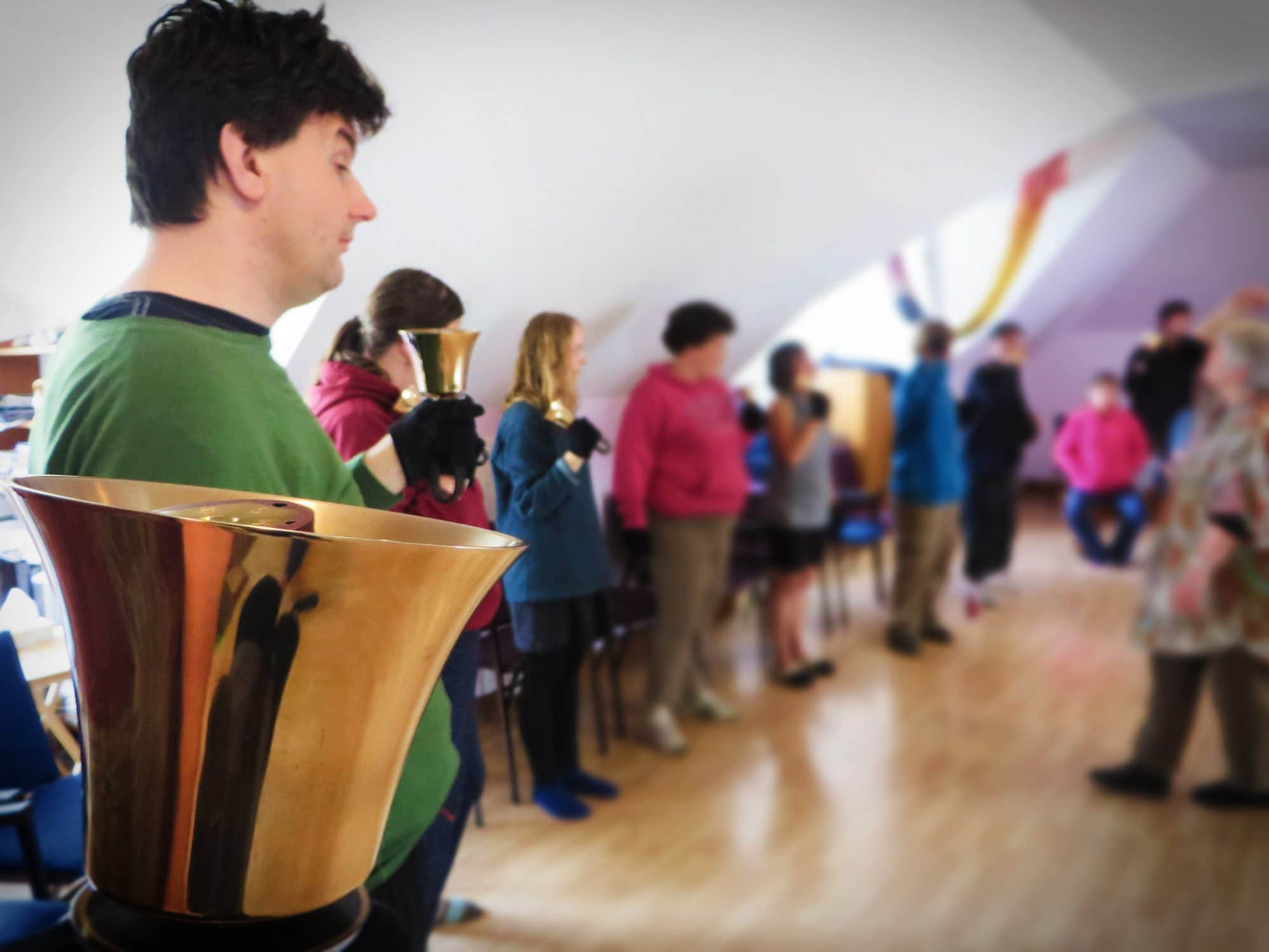A handbell choir stands in a line, ready to play their bells.