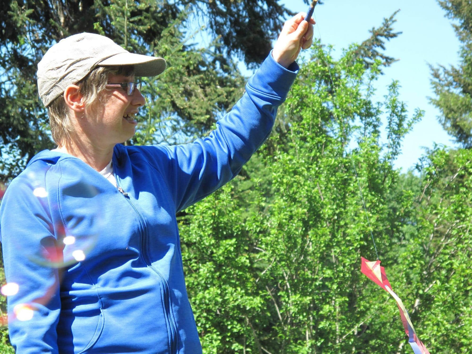 A woman wearing a white hat and a blue sweater is holding up a kite. She is standing in front of trees.