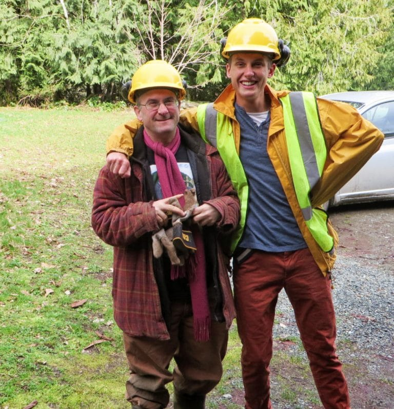 Two men stand together wearing yellow hard hats and reflector vests. They are laughing.