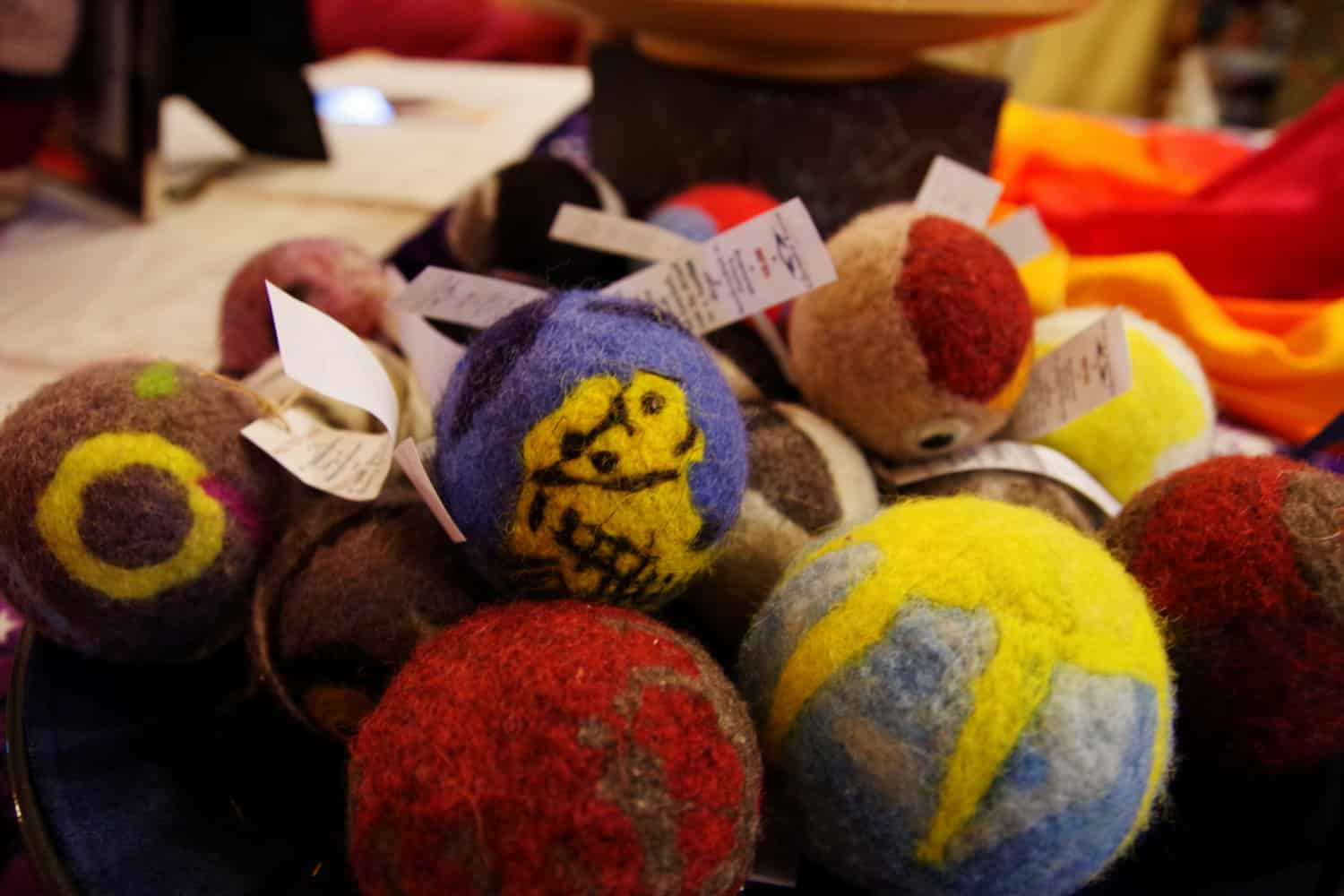 A colorful pile of felted balls with designs on them.