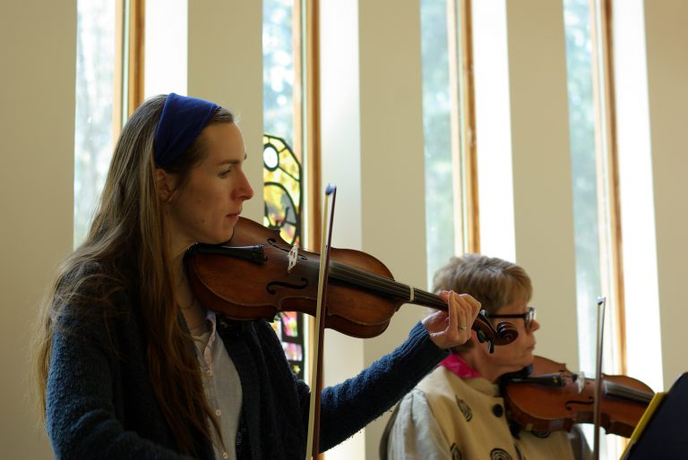 Two women play violins.
