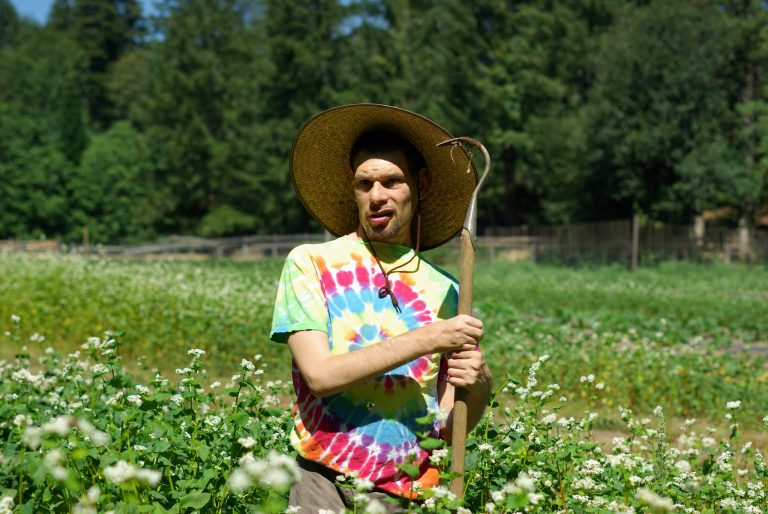 A young man stands in a field of tall grass wearing a tye dye shirt, a straw hat and holding a garden tool.