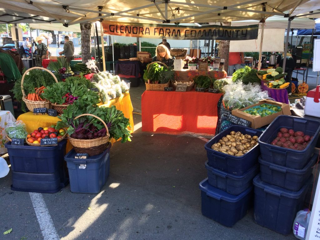 A market stand overflows with fresh produce at a local farmer's market.