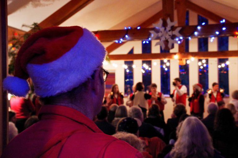A man in a santa hat watches a handbell choir perform underneath Christmas lights.